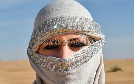 woman with veil in the desert
