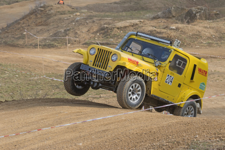 yellow off road car is jumping