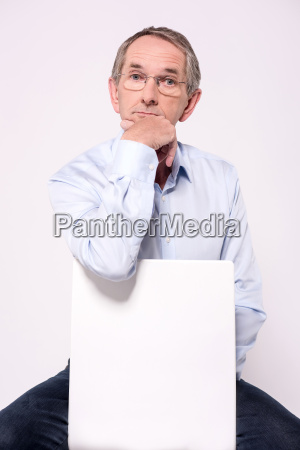thoughtful senior man siting behind pacard