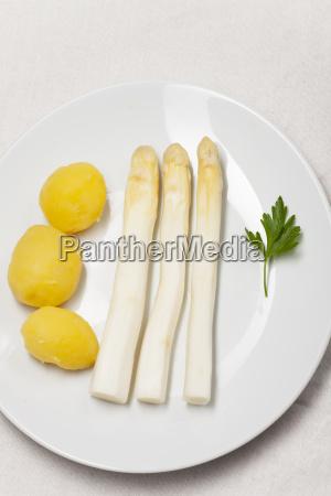 weisser spargel mit kartoffeln auf einem