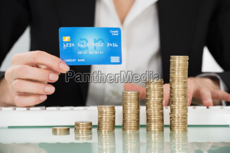 businesswoman holding credit card with stacked
