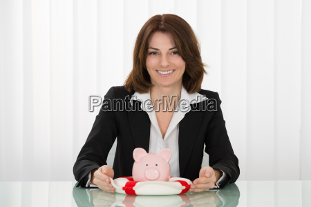 businesswoman sheltering piggybank with lifebelt