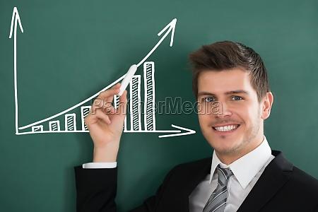 happy businessman holding chalk