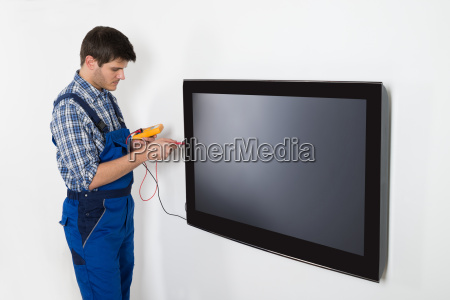 technician repairing television with multimeter