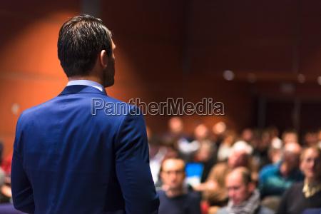 public speaker giving talk at business
