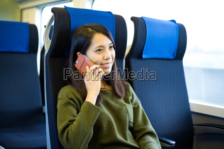 woman talk to cellphone inside train