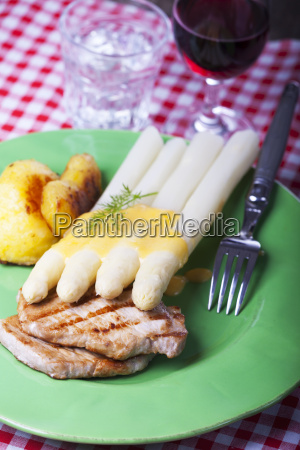 white asparagus and pork steak on