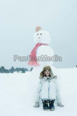menina adolescente encostado boneco de neve