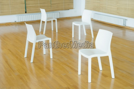 four empty chairs on hardwood floor