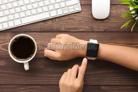 hand using smartwatch on desk top