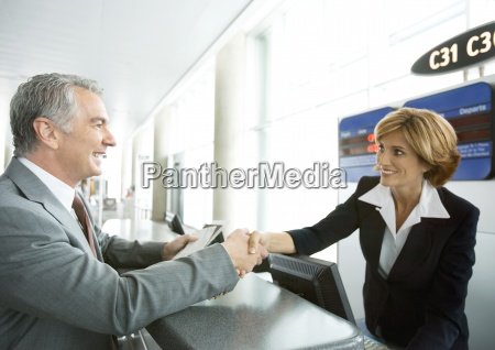 airline attendant shaking hands with passenger
