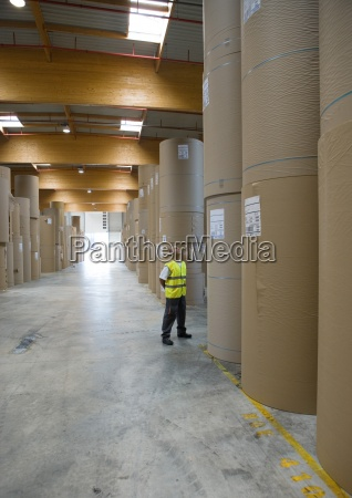 factory worker standing next to rolls