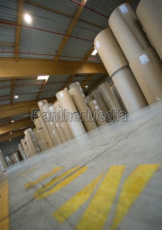 warehouse containing rolls of paper