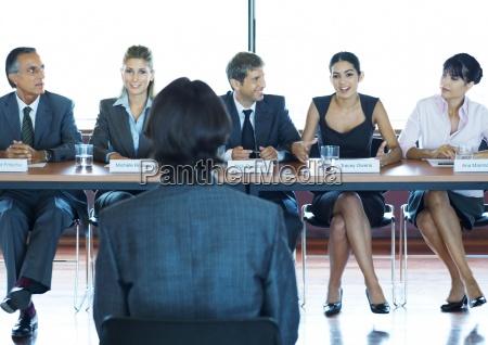 businesspeople in committee meeting facing man