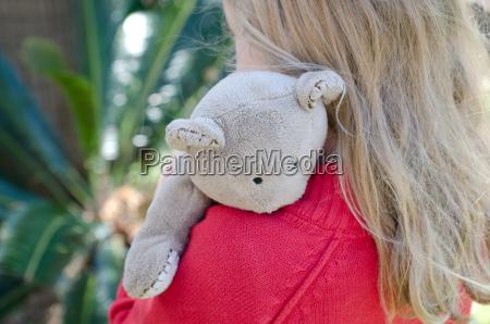 little girl hugging her teddy tightly