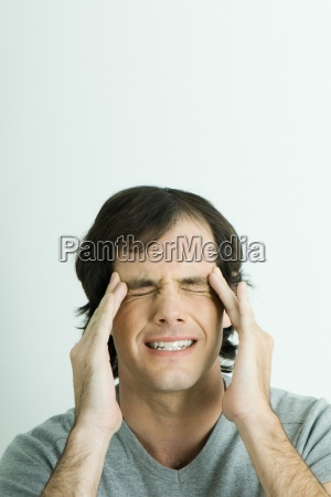 man holding sides of head and