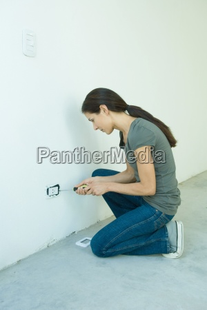 woman replacing outlet cover