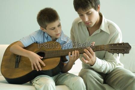 man teaching boy to play the