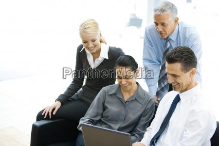 four business associates looking at laptop