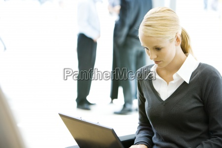 young businesswoman using laptop computer looking