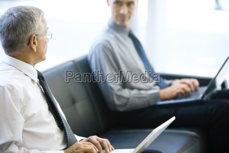 two businessmen sitting on sofa looking