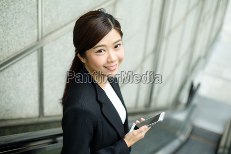 businesswoman going down escalator