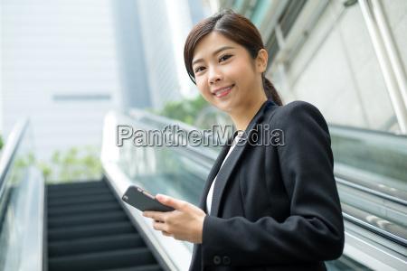 businesswoman going up to escalator