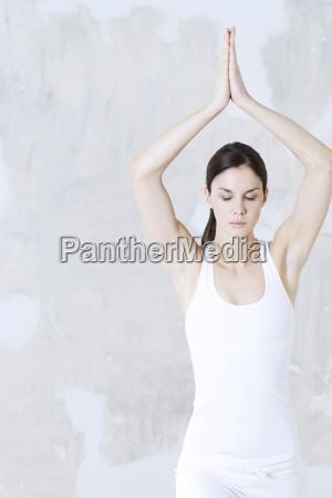 young woman doing yoga pose arms