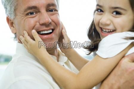 man holding up little girl girls