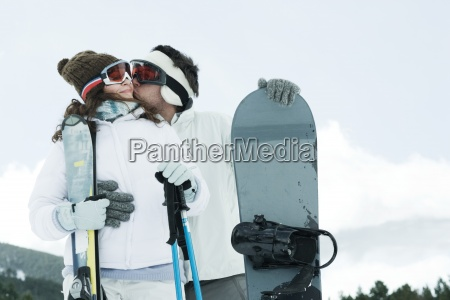 young couple standing outside with skis