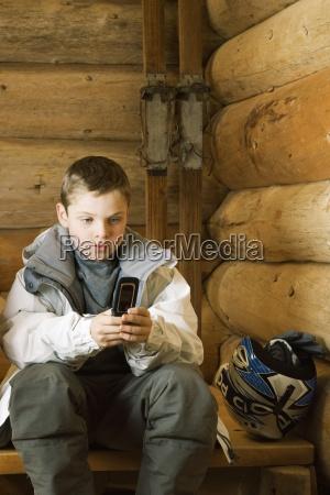 boy in ski gear sitting using
