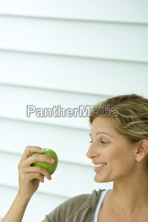 woman holding up apple and smiling