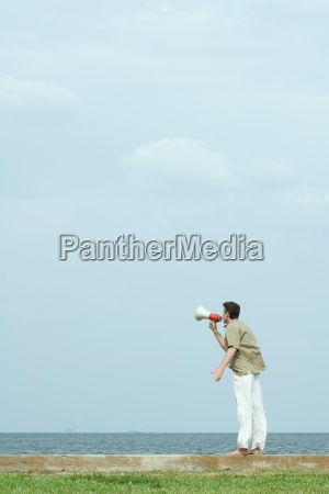 man standing by the sea shouting