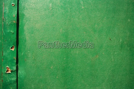 green painted surface with holes close
