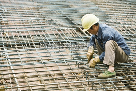 man crouching at construction site building
