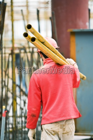 worker at construction site carrying metal
