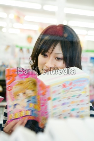 young woman reading manga style comic