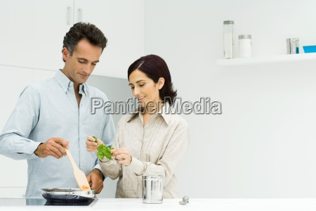 couple cooking together woman holding fresh