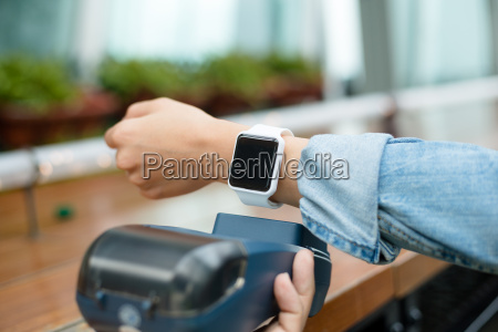 customer using wearable watch to pay