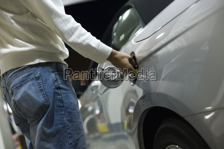 driver opening gas tank to refuel