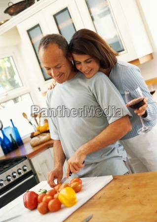couple in kitchen man cutting vegetables