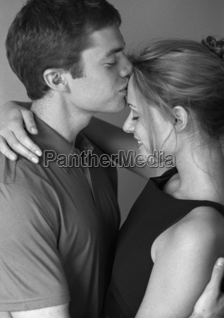 couple embracing man kissing womans forehead