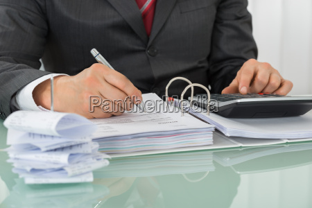 businessman calculating tax at office desk
