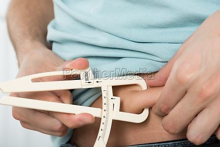 man measuring stomach fat