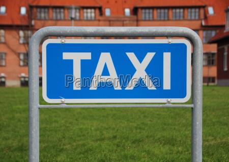 taxi sign closeup with building and