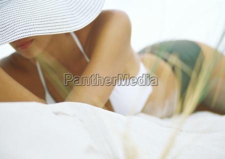 woman lying on sand wearing bikini