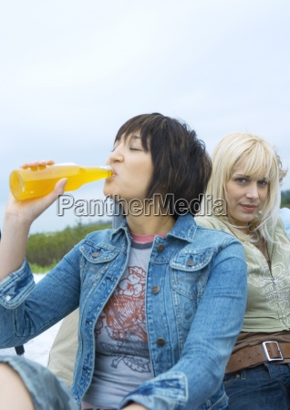 young woman drinking orange soda