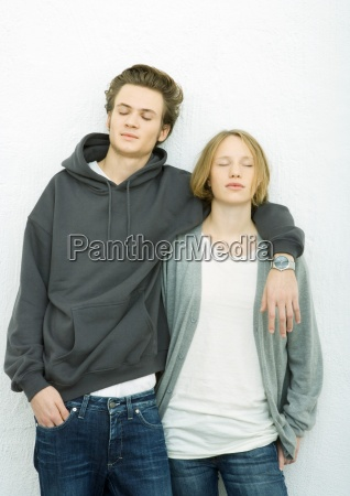 young couple leaning against wall mans