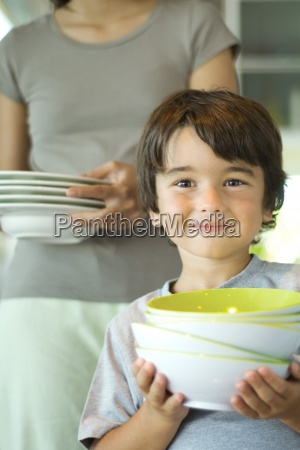 mother and son carrying dishes together