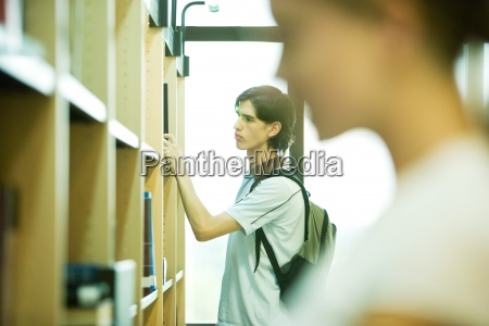 students looking at shelves in college